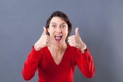 Ekstatische junge Frau, die mit den Daumen oben nach Aufregung schreit Stockfotos