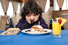 Ekstatischer junger Junge, der einen Stapel Pfannkuchen isst Lizenzfreies Stockbild