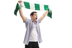 Ekstatisches Fußballfan, das einen Schal und ein Zujubeln hält stockfotos