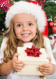 Ekstatisches glückliches Mädchen mit Weihnachtsgeschenk Lizenzfreie Stockfotos