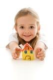 Ekstatisches kleines Mädchen mit ihrem Lehmhaus Stockbild