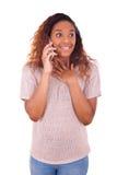 Ekstatyczna młoda amerykanin afrykańskiego pochodzenia kobieta robi rozmowie telefonicza na ona Obraz Royalty Free