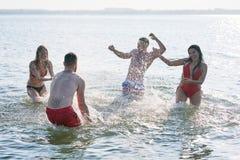 Ekstatyczni przyjaciele bryzga jezioro wodę zdjęcia royalty free