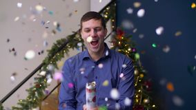 Ekstatyczny mężczyzna wybucha boże narodzenie confetti krakers zbiory