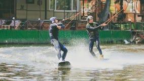 Ekstremum park, Kijów, Ukraina, 07 może 2017 - kilka młodzi człowiecy jechać Wakeboard, sztuczki i krótkopęd kamera Fotografia ad Fotografia Stock