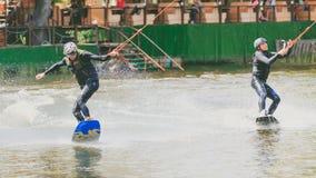 Ekstremum park, Kijów, Ukraina, 07 może 2017 - kilka młodzi człowiecy jechać Wakeboard, sztuczki i krótkopęd kamera Fotografia ad Obraz Royalty Free