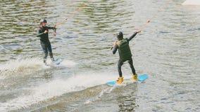 Ekstremum park, Kijów, Ukraina, 07 może 2017 - kilka młodzi człowiecy jechać Wakeboard, sztuczki i krótkopęd kamera Fotografia ad Obrazy Royalty Free