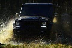 Ekstremum, wyzwanie i 4x4 pojazdu pojęcie, SUV lub offroad samochód na ścieżce zakrywającej z trawy kałuży z wodą skrzyżowaniem fotografia stock