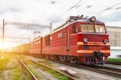 Eléctrico locomotor rojo con un tren de carga en la velocidad monta por el carril imagen de archivo libre de regalías