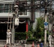 elétrico O homem de funcionamento repara um mau funcionamento bonde na fiação TAILÂNDIA BANGUECOQUE Imagem de Stock Royalty Free