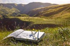 El álbum con una imagen del paisaje miente en la tierra contra el contexto del paisaje de las montañas kazakhstan imagen de archivo