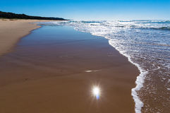 El ángulo bajo de la costa tiró con la reflexión del sol en agua Imágenes de archivo libres de regalías