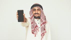 El árabe sonriente en vestido nacional muestra smartphone y sonríe extensamente Un hombre muestra un teléfono moderno Asunto y of metrajes