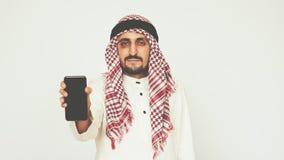 El árabe sonriente en vestido nacional muestra smartphone y sonríe El hombre muestra su pulgar para arriba Asunto y oficina Traba almacen de video