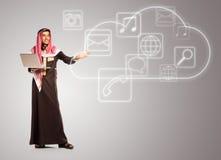 El árabe sonriente joven con el ordenador portátil muestra los iconos virtuales de la nube Imagen de archivo