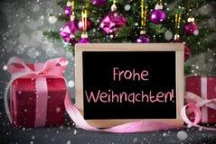 El árbol con los regalos, copos de nieve, Bokeh, Frohe Weihnachten significa Feliz Navidad Fotos de archivo