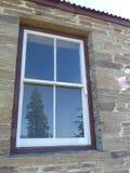 El árbol de la secoya reflejó en la ventana de piedra histórica de la cabaña, Nueva Zelanda fotografía de archivo libre de regalías