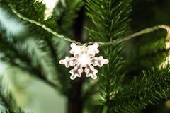 El árbol de navidad adornó una guirnalda con las luces del copo de nieve Fotos de archivo libres de regalías