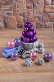 El árbol de navidad de bolas se está colocando en un cuenco de mimbre Imagen de archivo libre de regalías