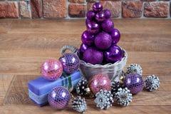 El árbol de navidad de bolas se está colocando en una cesta de mimbre Imágenes de archivo libres de regalías