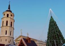 El árbol de navidad con las decoraciones y el campanario en la catedral ajustan Imagenes de archivo