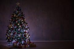 El árbol de navidad con las luces y las guirnaldas y los regalos se dirigen para la Navidad Foto de archivo
