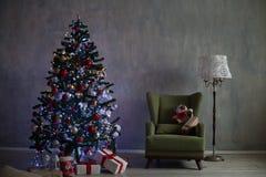 El árbol de navidad con las luces y las guirnaldas y los regalos se dirigen para la Navidad Fotografía de archivo