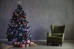 El árbol de navidad con las luces y las guirnaldas y los regalos se dirigen para la Navidad Imágenes de archivo libres de regalías