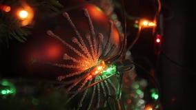 El árbol de navidad con los juguetes, una guirnalda eléctrica está en el árbol, bola roja de la Navidad, primer almacen de metraje de vídeo