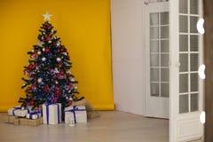 El árbol de navidad con los presentes, guirnalda enciende Año Nuevo Foto de archivo