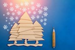 El árbol de navidad cortado del papel y la nieve del garabato forman escamas en azul Foto de archivo