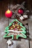 El árbol de navidad del pan de jengibre con canela de la vela protagoniza el bulbo de la Navidad de la ramita del pino en piso de Foto de archivo