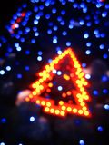El árbol de navidad en fondo negro con el bokeh azul se enciende Fotos de archivo