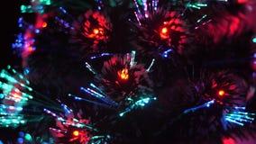 El árbol de navidad en sitio brilla con las luces azules, rojas el árbol de navidad artificial se adorna con una guirnalda y bril almacen de video