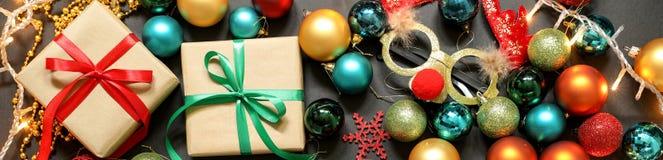 El árbol de navidad juega las bolas, regalos, máscara de los ciervos en fondo oscuro Fotografía de archivo