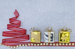 El árbol de navidad rojo de la cinta con la caja hermosa de la meta y de regalo de la plata en el brillo de plata texturiza el fo Imagen de archivo