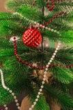 El árbol de navidad se adorna con las gotas y una cuenta de cristal roja Globo del ` s del Año Nuevo, con la superficie desigual  Foto de archivo libre de regalías