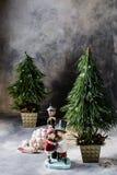 El árbol de navidad, una figura de cerámica, la Navidad juega en un fondo gris con un divorcio Fotografía de archivo libre de regalías