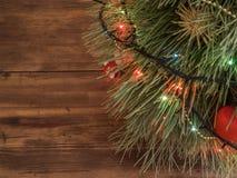 El árbol de navidad verde adornado con los juguetes y la guirnalda llevó luces en la picea festiva de la tabla de madera Imágenes de archivo libres de regalías