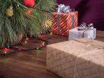 El árbol de navidad verde adornado con los juguetes y la guirnalda llevó luces Encajona los regalos Fotografía de archivo