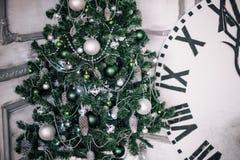 El árbol de navidad verde en el fondo es un reloj decorativo grande que muestra medianoche Fotografía de archivo
