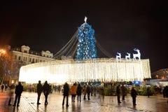 El árbol del grupo de personas y del Año Nuevo en el fondo Foto de archivo