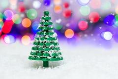 El árbol del juguete asperjado con nieve se coloca en la nieve en el fondo del bokeh imagen de archivo