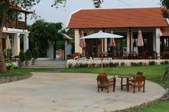 El área alrededor de la casa, el área vacía, el césped, las sillas a sentarse, el cielo hermoso foto de archivo libre de regalías
