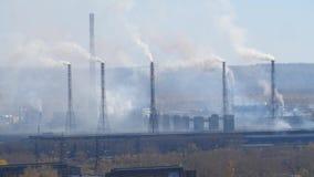 El área industrial con un tubo del humo grueso vertió de las chimeneas de la fábrica almacen de video