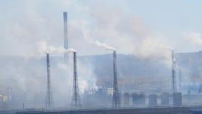 El área industrial con un tubo del humo grueso vertió de las chimeneas de la fábrica almacen de metraje de vídeo