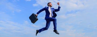 El éxito en negocio exige esfuerzos sobrenaturales Hombre de negocios con el salto de la cartera alto en el movimiento adelante H fotos de archivo libres de regalías