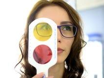 El óptico bonito del oftalmólogo del optometrista de la mujer joven realiza una prueba de la acromatopsia foto de archivo libre de regalías