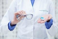 El óptico femenino experto está mostrando los nuevos vidrios fotos de archivo libres de regalías