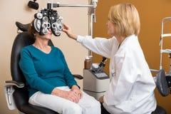 El óptico Using Phoropter To examina los ojos de la mujer fotos de archivo